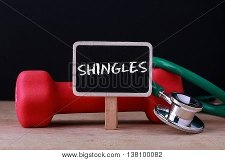 Medical concept - Stethoscope and dumbbell on wood with Shingles word