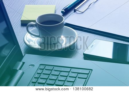 Office workplace with laptop, smart phone and coffee cup on table