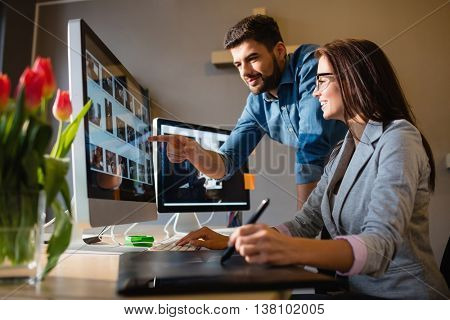 Graphic designer pointing at computer in office