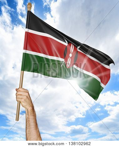 Person's hand holding the Kenya national flag and waving it in the sky, 3D rendering