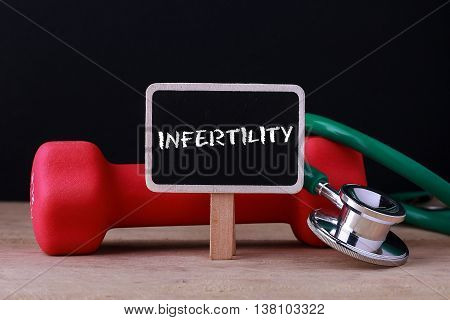 Medical concept - Stethoscope and dumbbell on wood with Infertility word