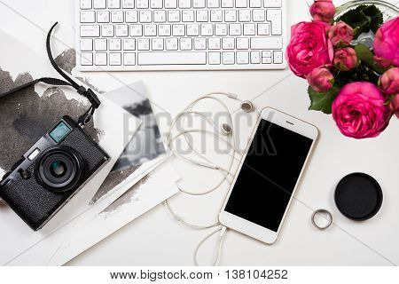 Modern computer keyboard, pink flowers and photo camera on white table, freelancer girl's workspace