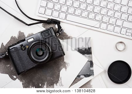 Styled tabletop with computer keyboard and retro camera on white background, photographer artist workspace