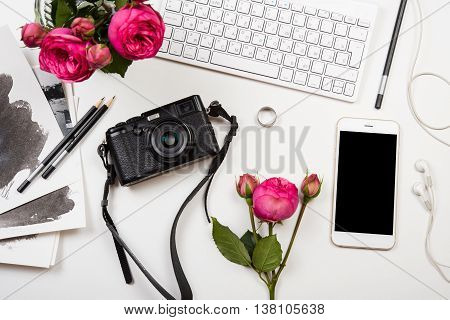 Modern smartphone, computer keyboard, pink flowers and photo camera on white table, freelancer girl's workspace