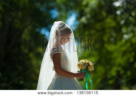 bride holds a wedding bouquet best day silhouette backlit