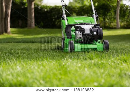 Outdoor shot of green lawnmower. Lawn mower