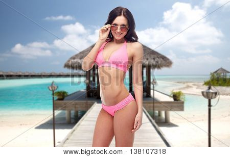 people, fashion, swimwear, summer and travel concept - happy young woman in sunglasses and pink swimsuit looking at you over maldives beach with bungalow background
