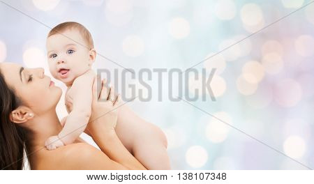 family, motherhood, parenting, people and child care concept - happy mother holding adorable baby over blue holidays lights background
