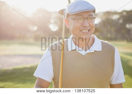 Sportsman holding his golf club and looking away on a field