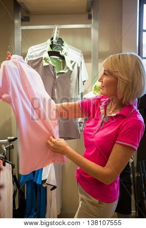 Sportswoman looking a polo shirt in a store