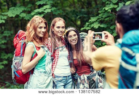 travel, tourism, hike, technology and people concept - group of smiling friends walking with backpacks taking picture by smartphone in woods