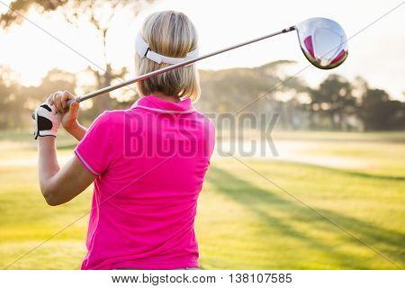 Rear view of sportswoman playing golf on field