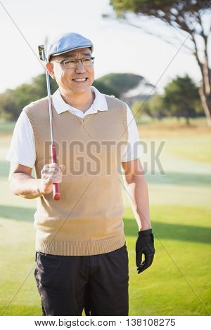 Portrait of sportsman holding his golf club and looking away on a field