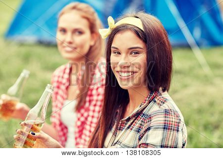 camping, travel, tourism, hike and people concept - happy young women with glass bottles drinking cider or beer at campsite