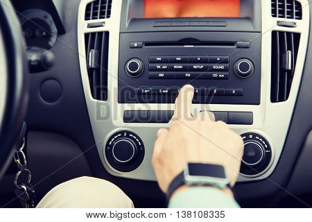 transport, road trip, car driving, technology and people concept - close up of male hand turning on radio on control panel system in car