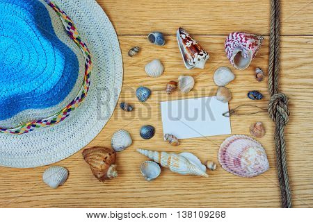 summer straw hat and seashells on a wooden table vacation concept paper tag with rope