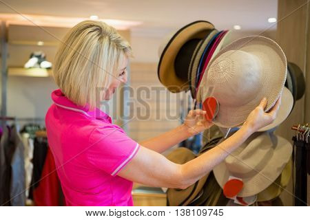 Mature woman looking a hat in a store