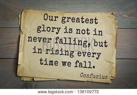 Ancient chinese philosopher Confucius quote on old paper background.  Our greatest glory is not in never falling, but in rising every time we fall.