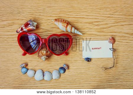 funny face from the sun glasses and seashells on a wooden table vacation concept paper tag with rope