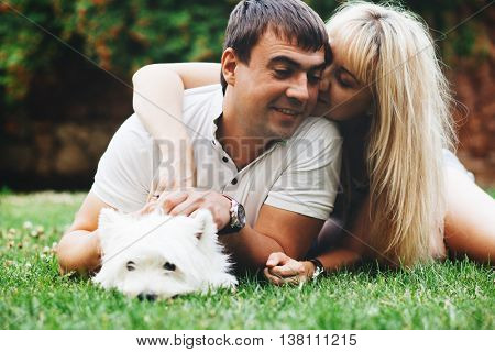 Young couple relaxing with English Highland White Terrier dog on grass in the backyard