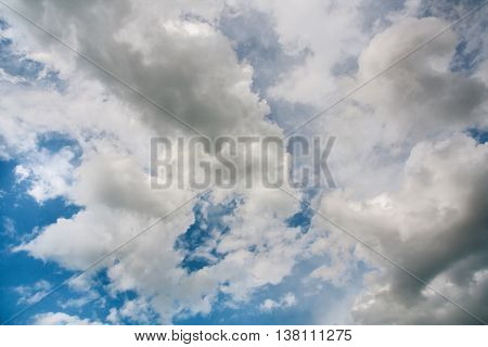 Landscape with white and gray cumulonimbus clouds in the blue sky