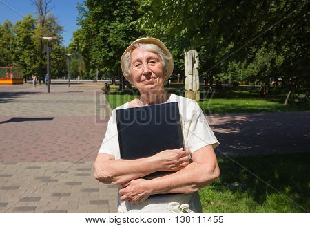 Senior woman with laptop in summer green park