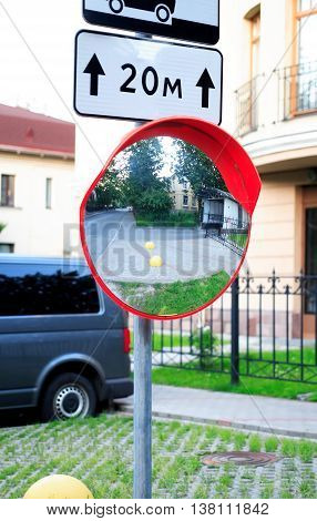 Urban scene. Closeup of metal pole with road sign and big circle mirror