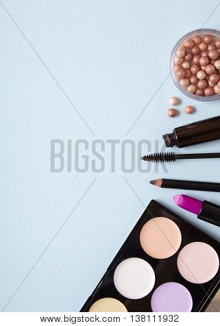 A selection of make up products arranged on a pastel blue background forming a page border