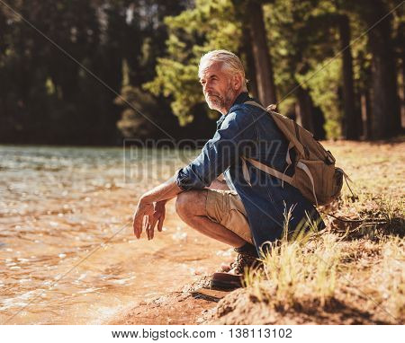 Mature Man Sitting Next To A Lake Admiring The View
