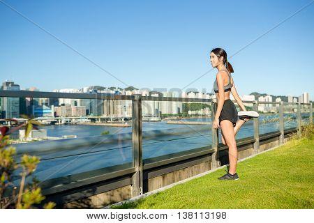 Woman runner stretching legs before run