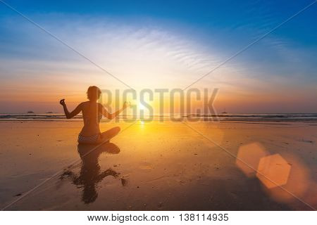 A girl sits on the beach in a yoga pose at sunset.