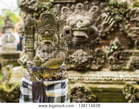 Traditional demon guards statue carved in stone on Bali.
