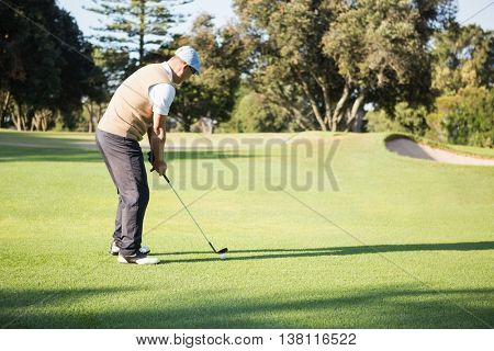Side view of sportsman playing golf on a field