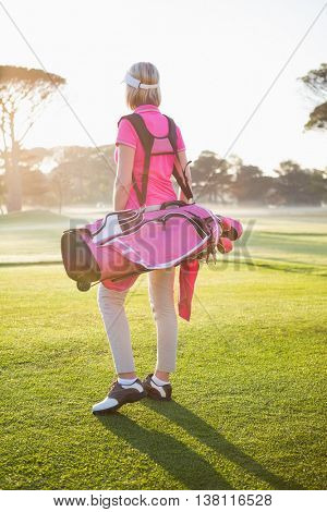 Rear view of sportswoman holding a golf bag on a field