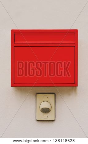 Red mailbox with doorbell on wall, vertical composition