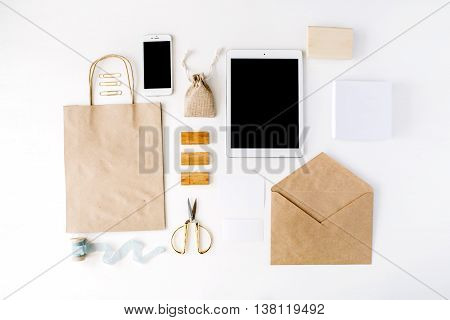 desk workspace with tablet phone craft envelopes on white background. flat lay top view