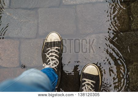 Male legs in sneakers and blue jeans walking through the rain puddle top view
