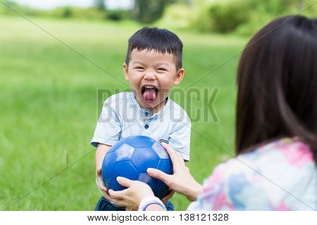 Little boy play soccer ball with his mother