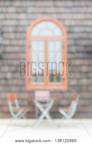 Blurred photo of chairs and table on porch with retro widow and brick front home background.