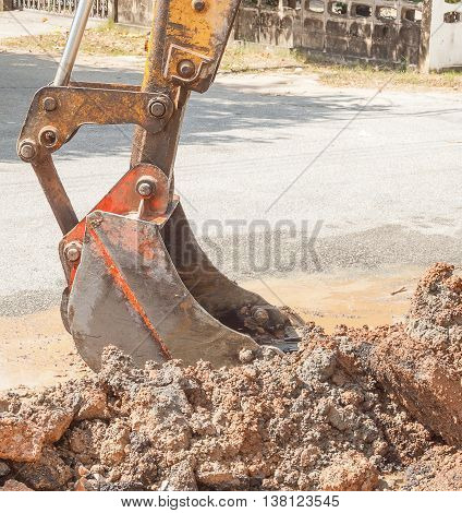 Excavator, bulldozer work a dig hole the repair of pipe water and sewerage on road