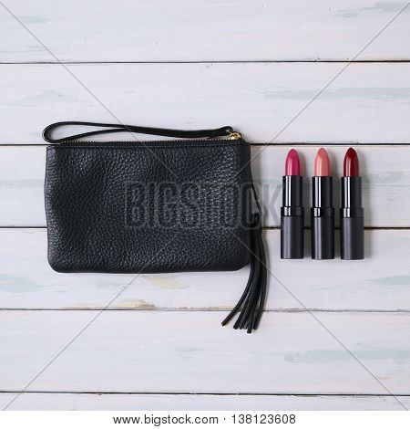 A black leather purse and lipsticks on a wooden background