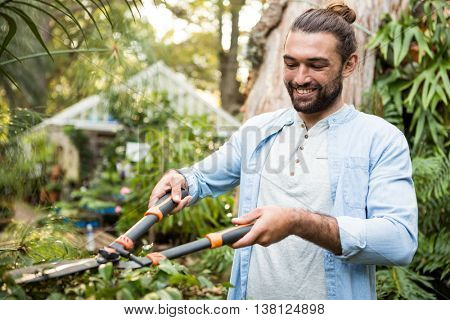 Happy young male gardener using hedge clippers at community garden