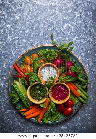 Veggie crudite platter with three different dips on the metal background