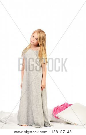 Cute little girl in a long nightie standing on her bed. Healthcare, beauty. Isolated over white. Copy space.