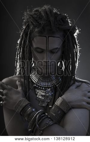 Young man's portrait. Stylish handsome sexy Guy with Dreadlocks and ethnic Jewelry Accessories (necklace bracelet) Close-up face. Tribal Style. Trendy egypt youthful man's look war paint