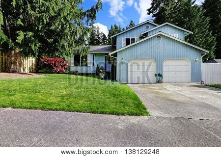 House Exterior. Classic American Blue House With Two Garage Spaces And Driveway