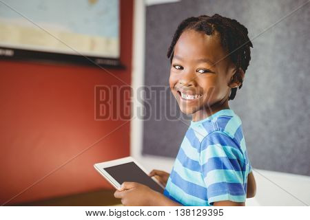 Portrait of schoolboy holding digital tablet in classroom at school