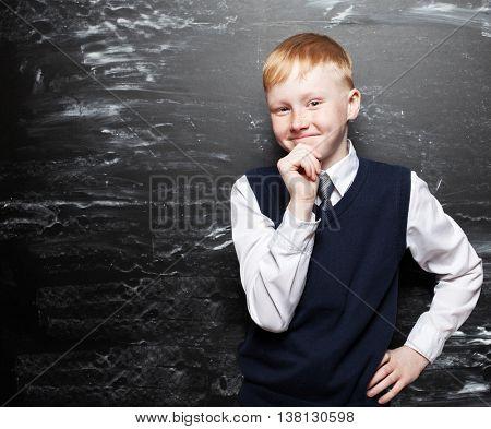 Boy near blackboard. Thinking Child at school. Student at classroom