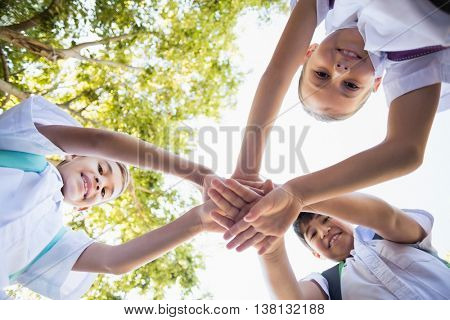 School kids stacking hands in campus at school