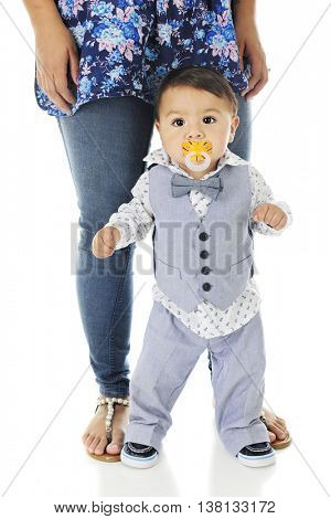 An adorable, dressed up baby boy, standing nervously against his mother's legs -- ready to walk, but feeling insecure.  On a white background.